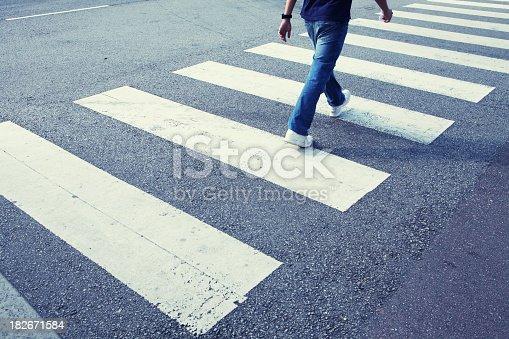 istock Man in jeans walking across a zebra crossing 182671584