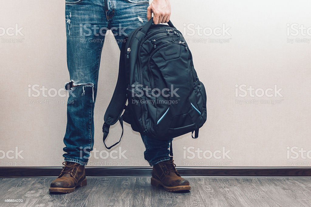 Man in jeans with backpack stock photo