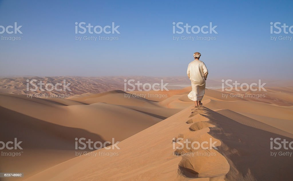 Man in kandura in a desert at sunrise​​​ foto
