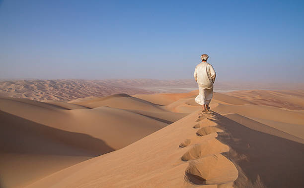 Man in kandura in a desert at sunrise Man in traditional outfit in a desert at sunrise saudi arabia stock pictures, royalty-free photos & images