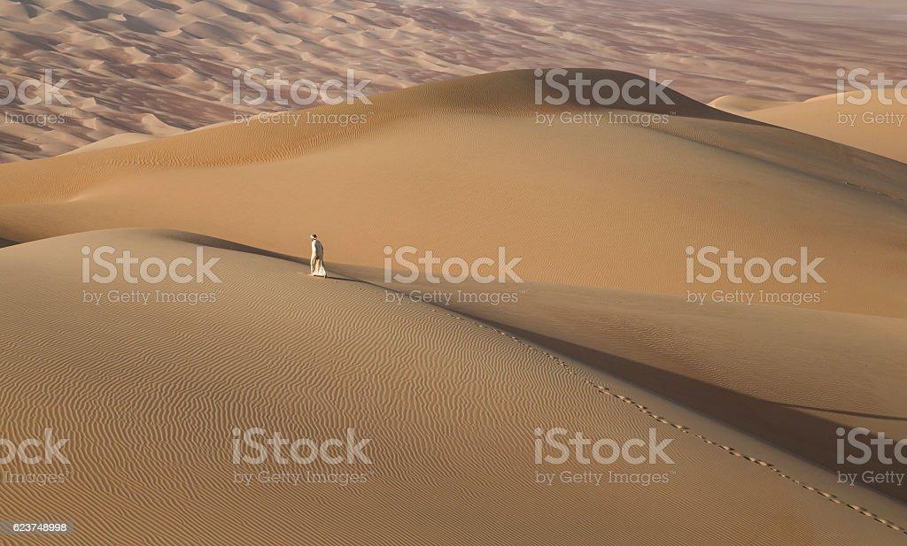 Man in kandura in a desert at sunrise stock photo