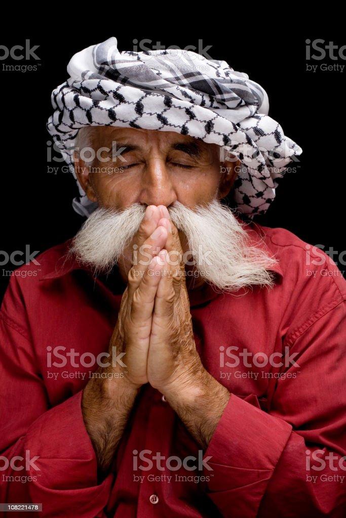 Man in keffiyeh praying royalty-free stock photo