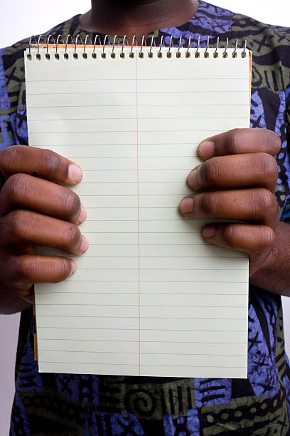 man in kente cloth shirt holding a blank writing tablet - kente cloth stock photos and pictures