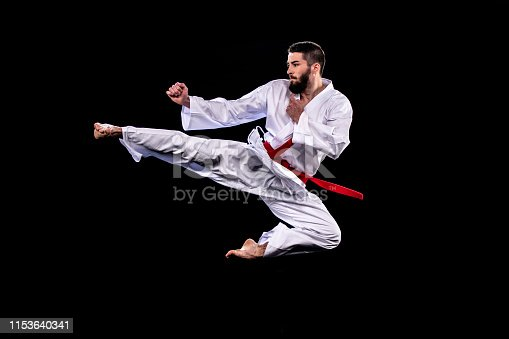 Male karate practitioner in mid-air during a flying kick. Black background.