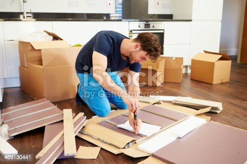 459373065 istock photo Man in kitchen of new house assembling furniture 459130441