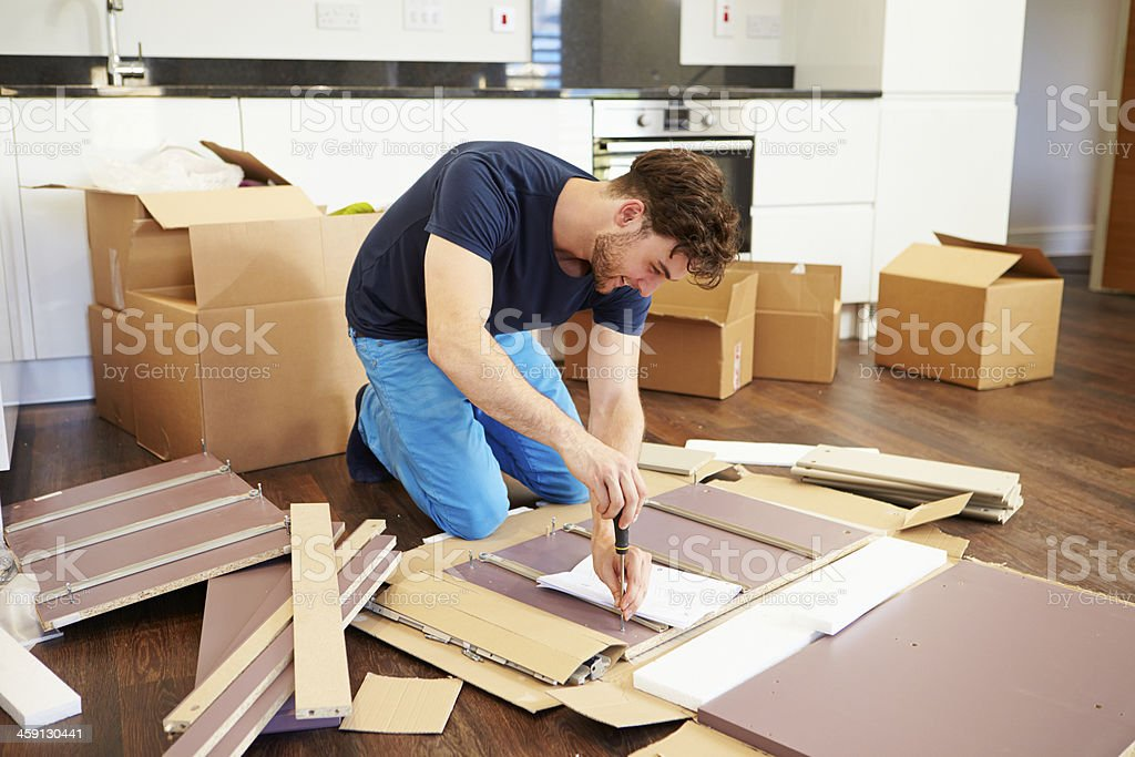 Man in kitchen of new house assembling furniture stock photo