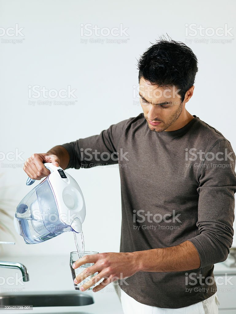 Man in kitchen pouring glass of water from jug stock photo