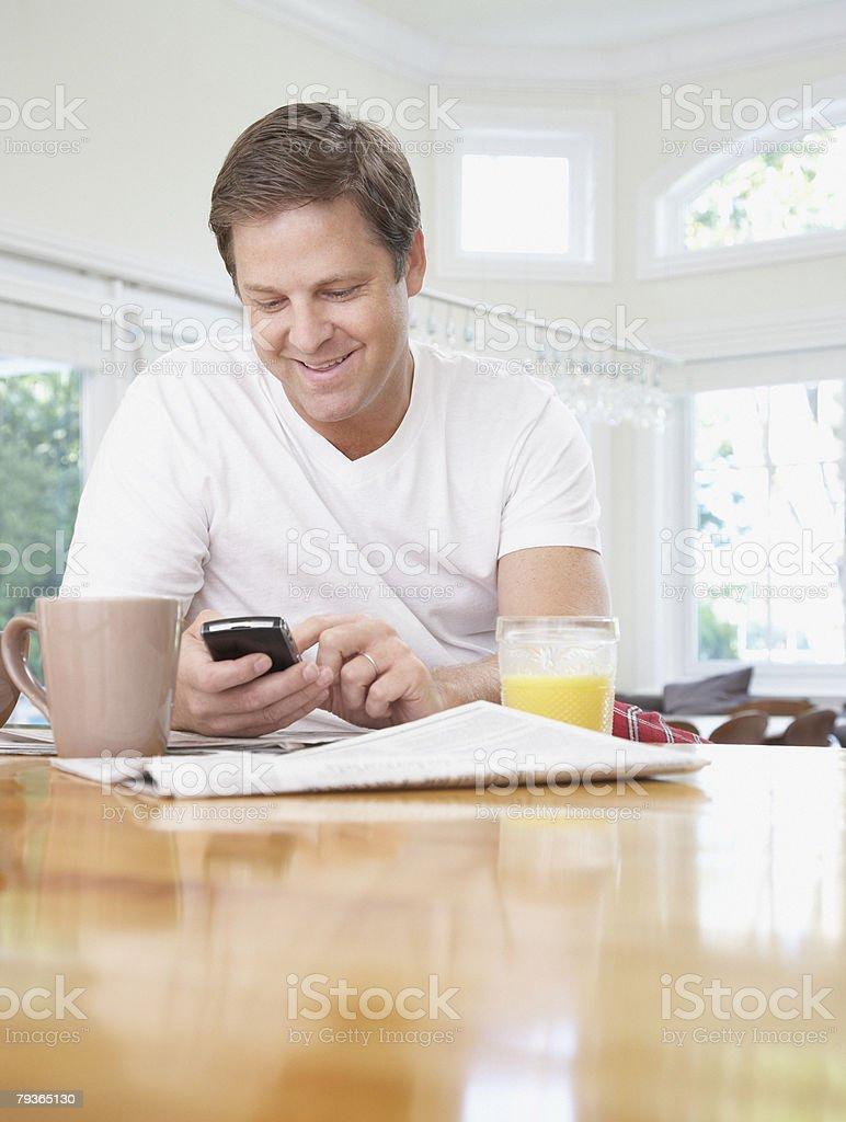 Homem na cozinha usando seu Telefone Móvel foto de stock royalty-free