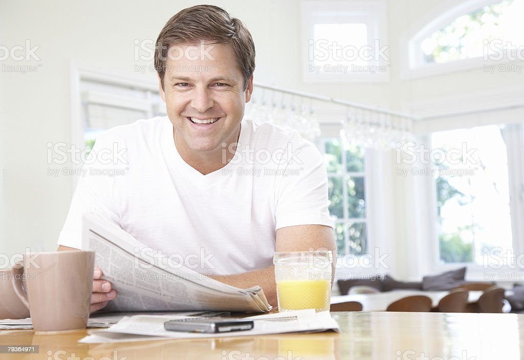 Man in kitchen with newspaper royalty-free stock photo