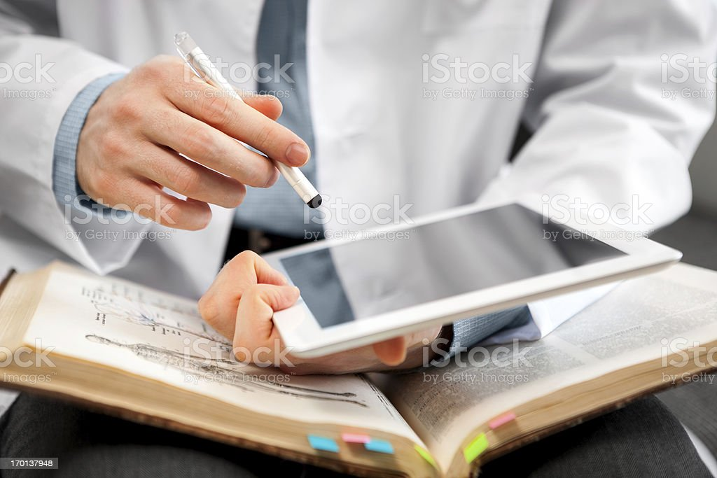 Man in lab coat using digital tablet and open book stock photo