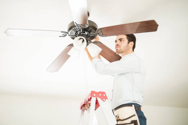 Man in ladder fixing ceiling fan Portrait of a busy handyman standing on a ladder and fixing a ceiling fan in a house ceiling fan stock pictures, royalty-free photos & images