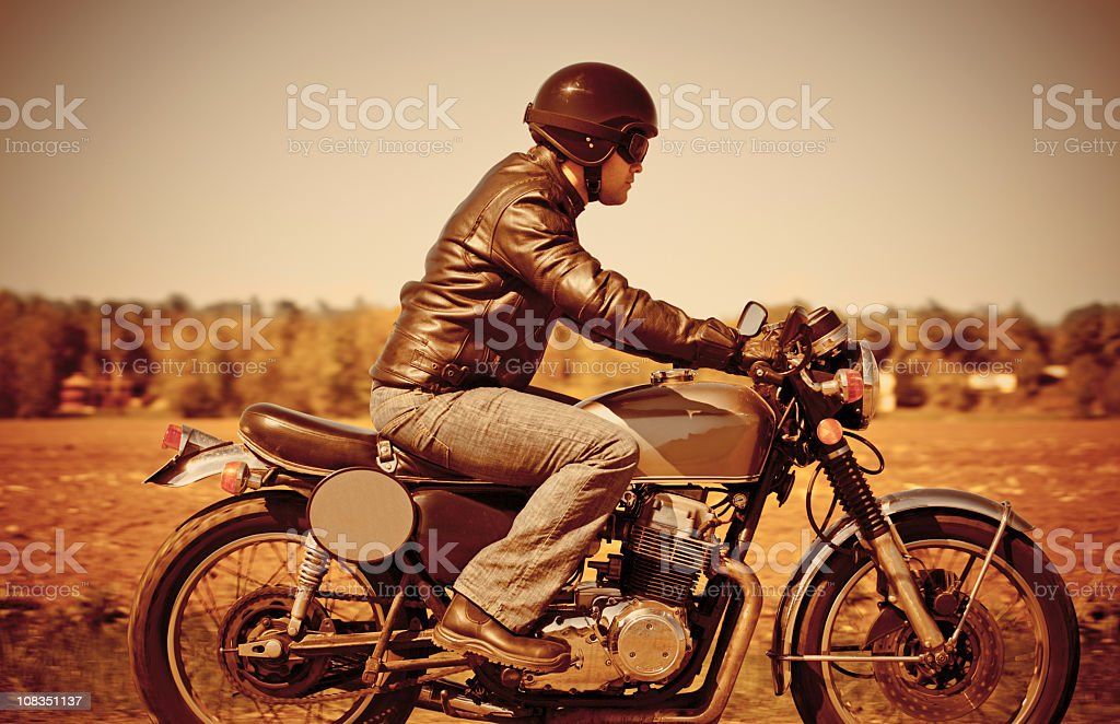 Man in leather jacket riding a vintage motorcycle stock photo