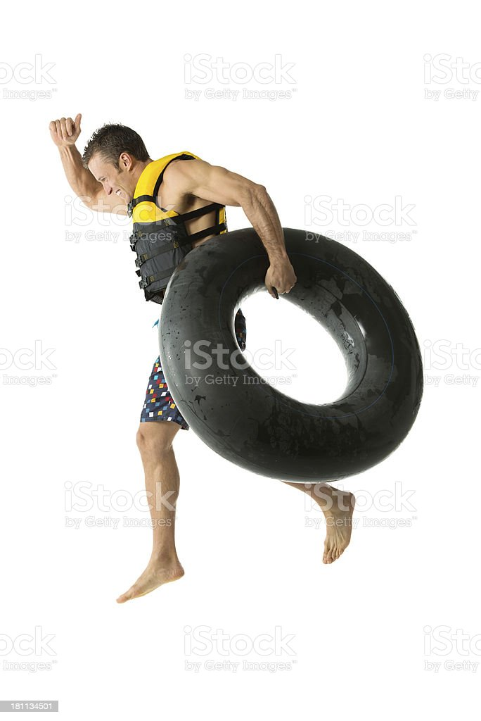 Man in life jacket jumping with a inner tube royalty-free stock photo
