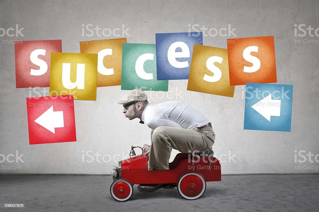Man in little car driving towards success stock photo