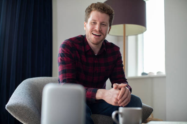 Man In Lounge At Home Asking Digital Assistant Question Man In Lounge At Home Asking Digital Assistant Question smart speaker stock pictures, royalty-free photos & images