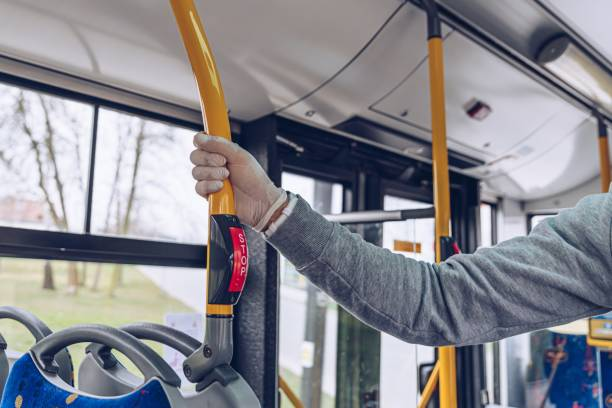 Man in mask and protective gloves traveling by city bus during coronovirus covid-19 stock photo