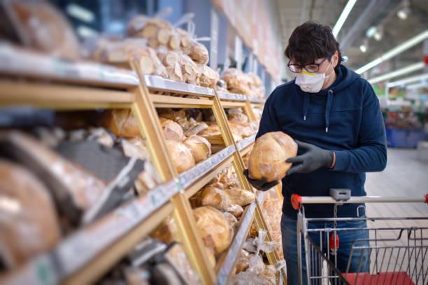 Mann in Maske und Gummihandschuhen bei der Auswahl des Brotes im Supermarkt – Foto