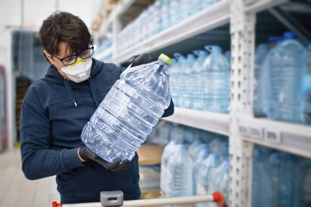 Man in mask and rubber gloves choosing huge bottle of water in a supermarket