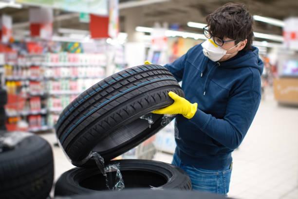 Mann in Maske und Gummihandschuhen bei der Auswahl von Reifen – Foto