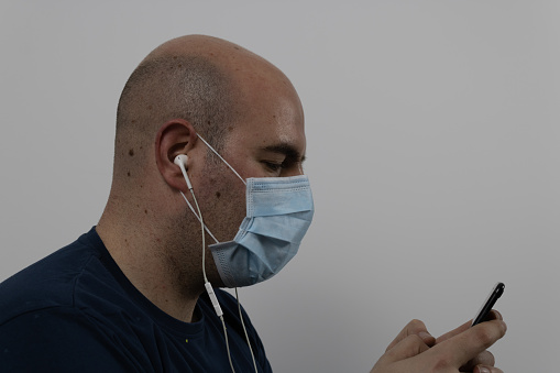 man in mask texting with cell phone