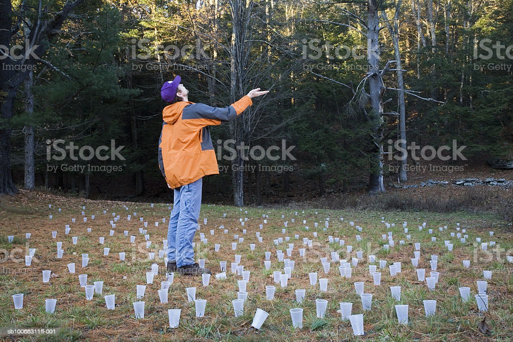 Man in meadow surrounded by plastic cups, holding out hand foto de stock libre de derechos