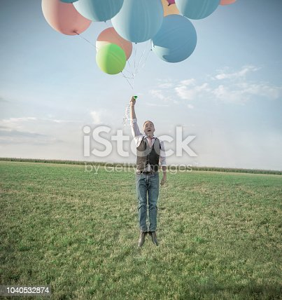 A man in a meadow has some balloons in his hand and is pulled up. picture with bright blue sky on a sunny day.