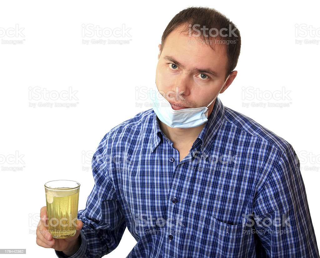 Man in medical mask dissolves a pill royalty-free stock photo
