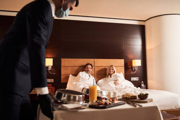 Man in medical mask pushing the trolley table with hotel breakfast stock photo