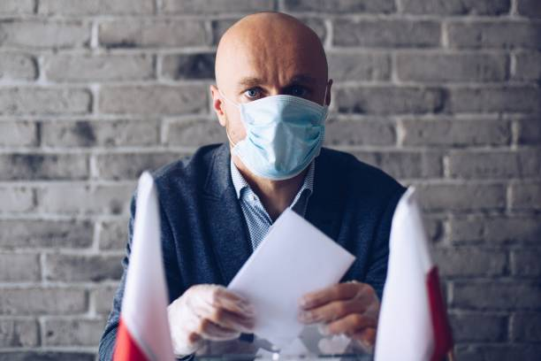 Mann in medizinischer Maske, der seine Stimme an die Wahlurne stellt. – Foto