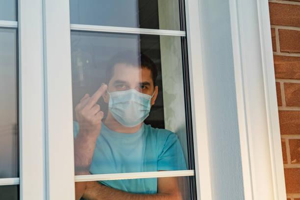 mens in medisch masker dat duimen omhoog teken toont fuck - avondklok stockfoto's en -beelden