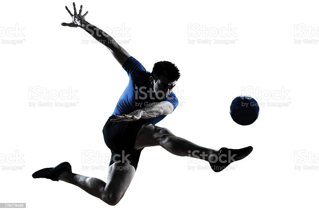 A man in mid air kicking a soccer ball royalty-free stock photo