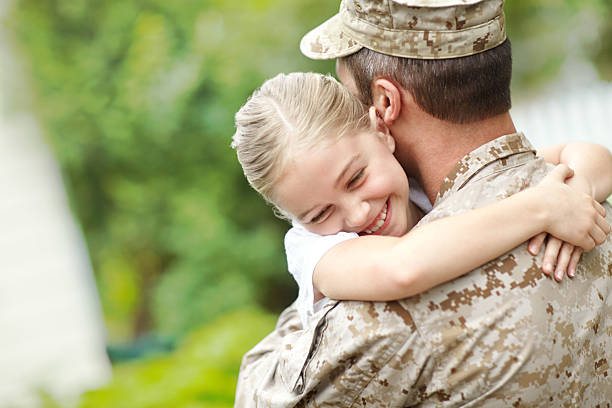 man in military uniform carrying a little girl - soldier stock photos and pictures