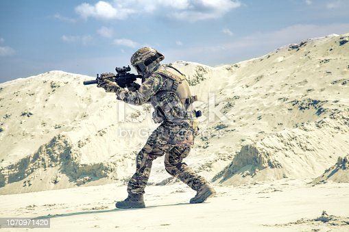 istock Man in military uniform playing airsoft in sands 1070971420