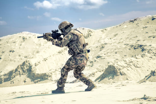 Man in military uniform playing airsoft in sands stock photo
