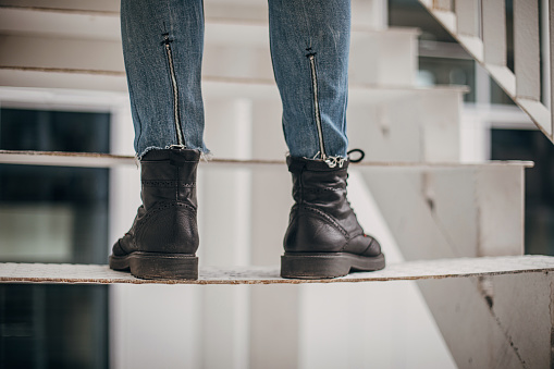 One man, modern man i leather boots and jeans standing on steps.