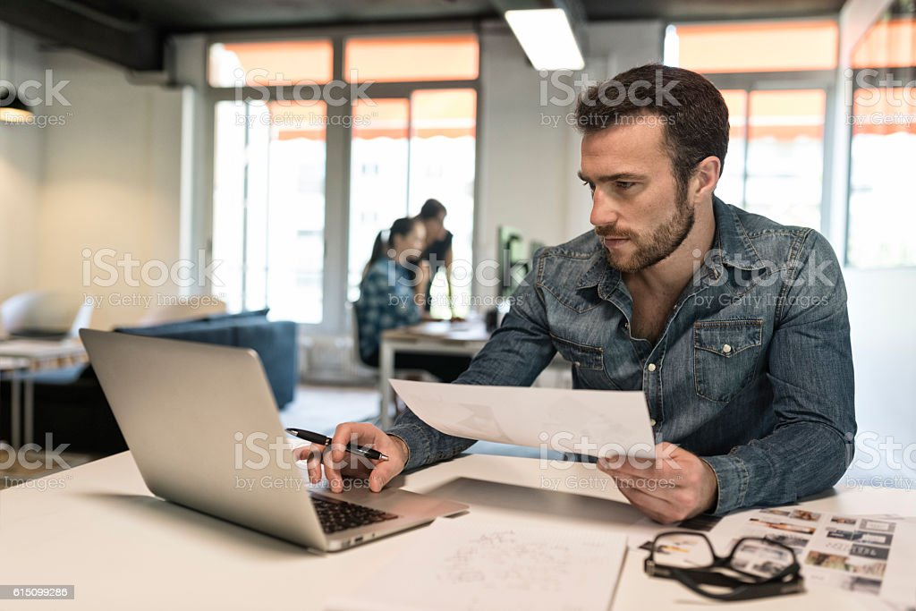 Man in modern office start-up working on laptop. stock photo