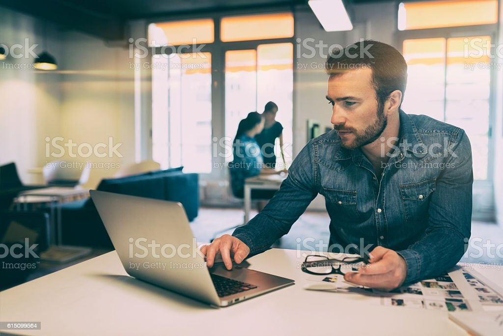 Man in modern office start-up working on laptop. stock photo