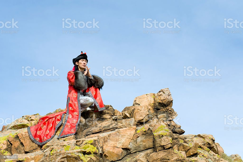 man in Mongolian costume on rock royalty-free stock photo