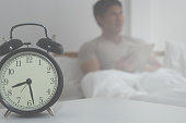 Man in morning bed with alarm clock counting late