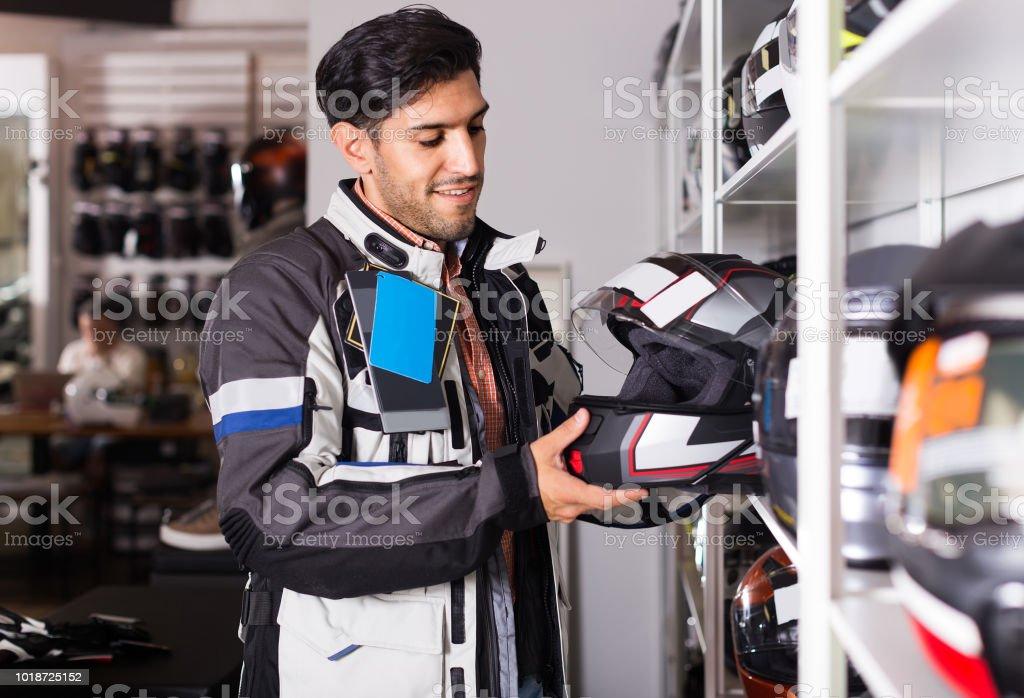 Homem em moto jaqueta é escolher novo capacete para a moto na loja. - foto de acervo