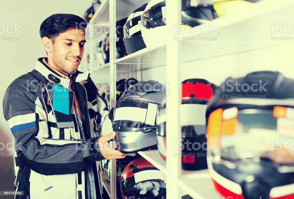 Man in moto jacket is choosing new helmet for motorbike in the store. royalty-free stock photo
