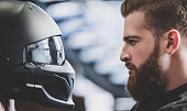 Handsome bearded man in motorcycle shop. Biker is choosing new vehicle and motorcycle accessories. Profile view of man looking on helmet. Safety driving concept.