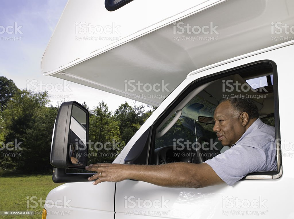 Man in motorhome, adjusting wing mirror Lizenzfreies stock-foto