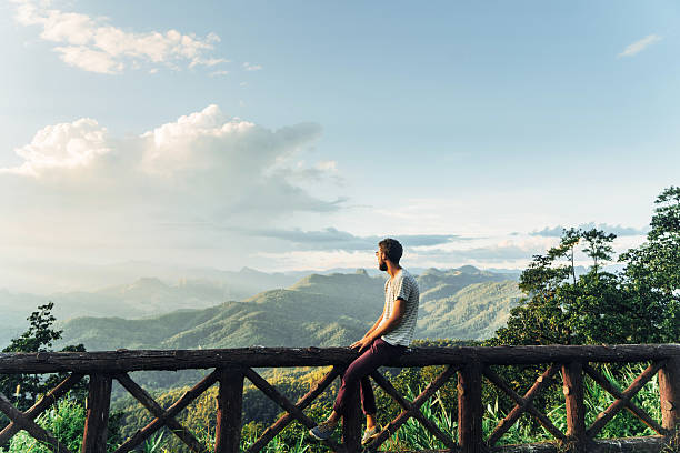 Man in mountains at sunset in Thailand Man on the background of beautiful sunset over green mountain hills in North of Thailand  explorer stock pictures, royalty-free photos & images