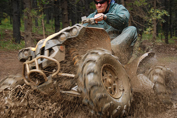 Man in mud on quad A quad coming out of the mud with lots of mud spray. quadbike stock pictures, royalty-free photos & images