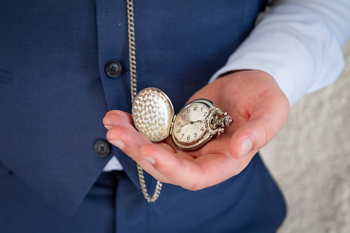 Man in navy blue suit holding pocket watch in hand
