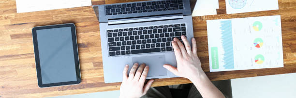 Mann im Büro gibt Daten aus Bericht in Laptop ein – Foto