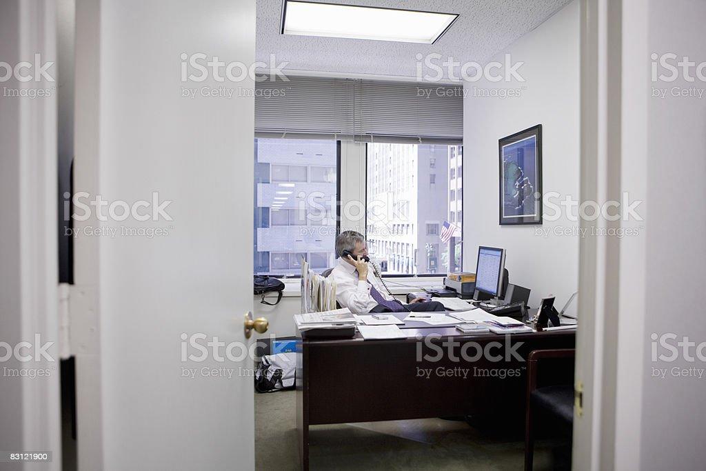 Uomo in ufficio sul telefono foto stock royalty-free