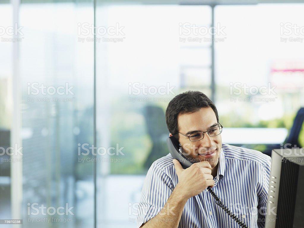 Man in office talking on telephone stock photo