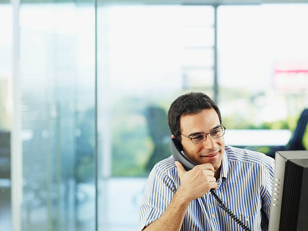 Man in office talking on telephone stock photo